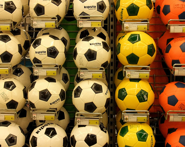 Photo of different coloured footballs on wall
