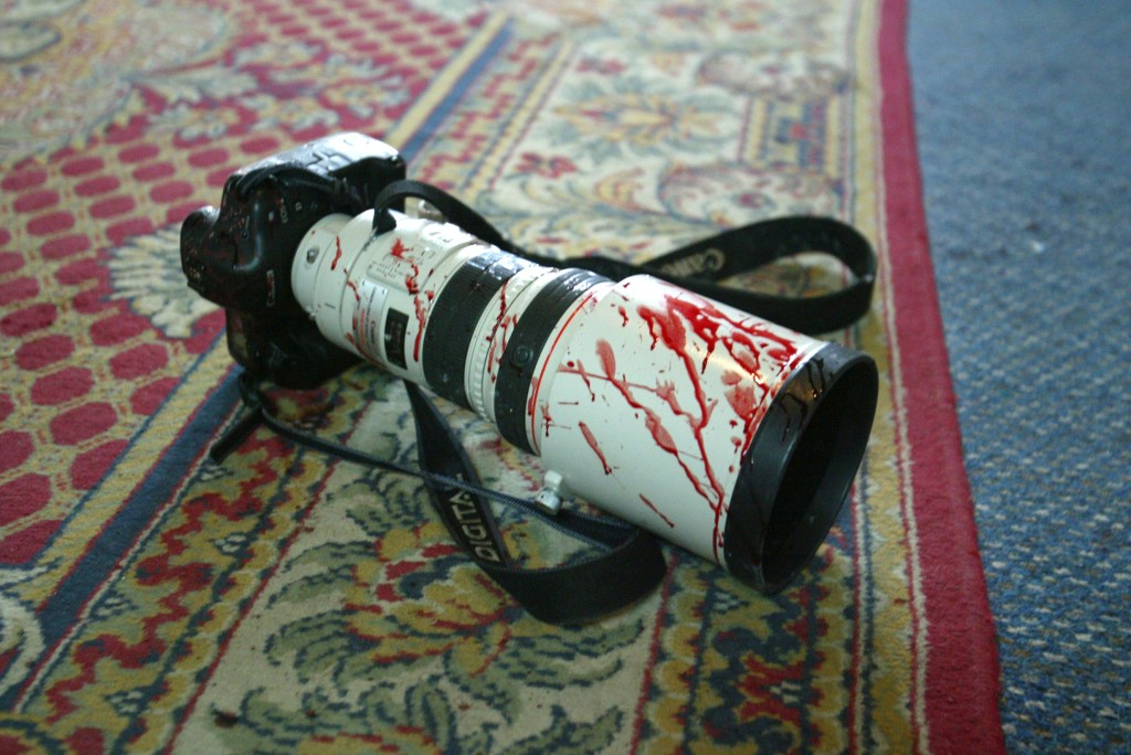 A camera covered with blood lies on a carpet