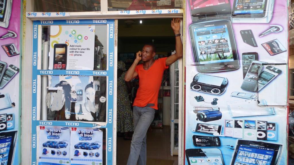 Man stands in doorway of mobile phone shop