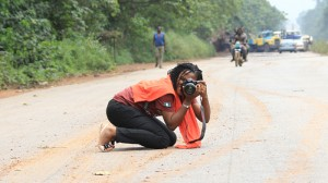 Phoro of a photographer kneeling on road taking photo