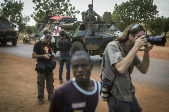Photographers take pictures of a tank in Mali