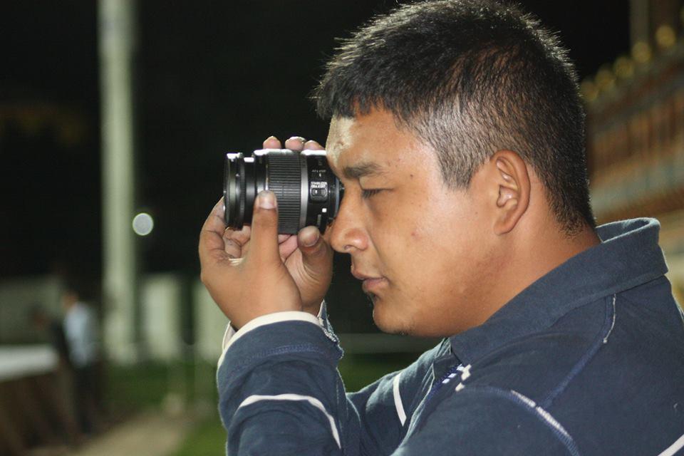 Tenzin looks through a camera lens